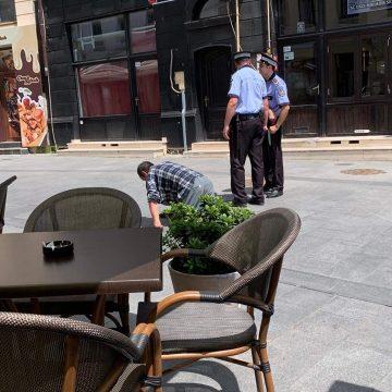 Bărbat în genunchi pe lângă poliţiştii locali